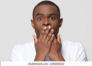 Shocked horrified african man covering mouth with hands feel scared looking at camera isolated on white studio background, startled black guy with surprised face afraid in silence, head shot portrait
