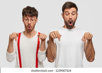 Shocked intensed young male friends point down on floor, gasp and stare with popped eyes, feel stunned, dressed in white neat clothes, stand closely against studio wall. Gosh, its embarrasing