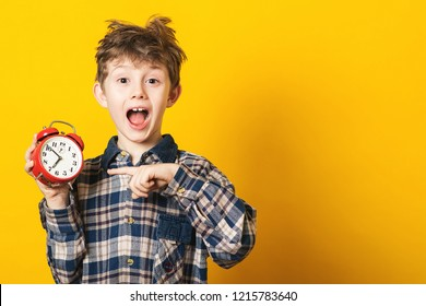 Schockierter Junge, der Wecker hält, Kopienraum. Kind einzeln auf gelbem Hintergrund. Zeit für die Schule. Kleiner Schüler hat verschlafen.Zeitkonzept. Aufgeregter Junge am Morgen. Kind, das auf Wecker zeigt
