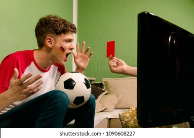 Shocked kid, red card in soccer game on TV, hand appears from TV set