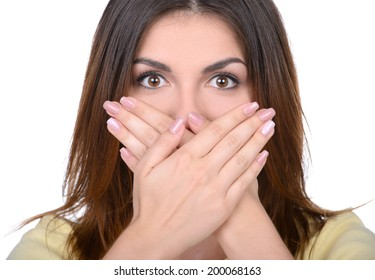 Shocked with the latest gossip. Beautiful young woman covering her mouth by the hands while standing isolated on white