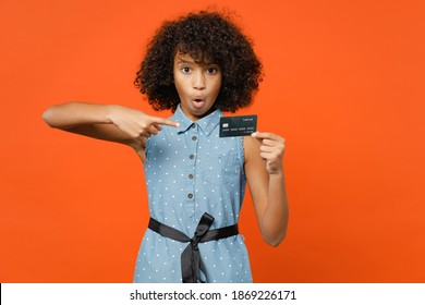 Shocked little african american kid girl 12-13 years old in denim dress pointing index finger on credit bank card isolated on orange background children studio portrait. Childhood lifestyle concept