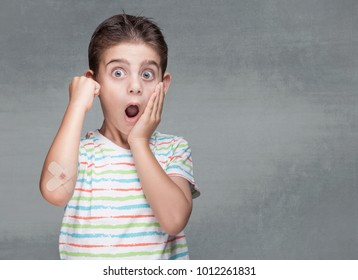 Shocked little boy with band aid on elbow
