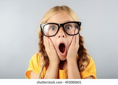 shocked little girl isolated on grey