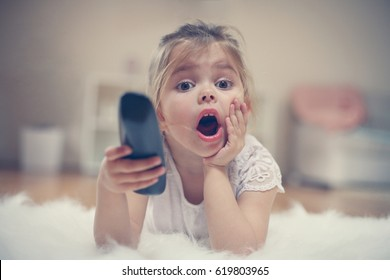 Shocked little girl watching TV lying on floor with remote control in hand.