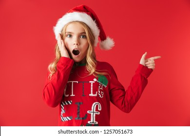 Shocked little girl wearing Christmas costume standing isolated over red background, pointing away
