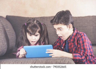 Shocked little kids react while watching inappropriate content on their tablet. Internet safety for kids concept.