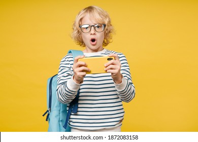 Shocked little male kid teen boy 10s years old wearing striped sweatshirt eyeglasses backpack play game on mobile phone isolated on yellow color background, child studio portrait. Education concept