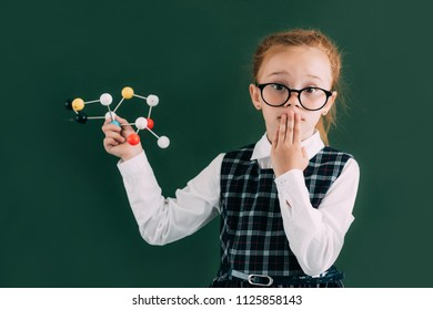 shocked little schoolchild holding molecular model and looking at camera while standing near chalkboard