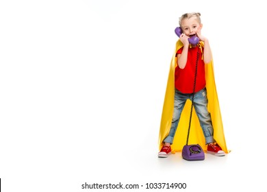 Shocked little supergirl wearing yellow cape and talking on phone isolated on white