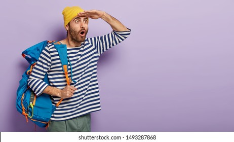 Shocked male backpacker carries tourist rucksack, enjoys journey alone, wears yellow hat and striped jumper, focused into distance with fright, has eyes popped out, likes exciting traveling.
