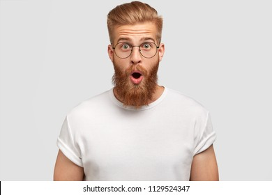 Shocked male blogger with trendy hairdo being stupefied as sees decrease of followers on his website, wears round glasses and t shirt, isolated over white background. People and emotions concept