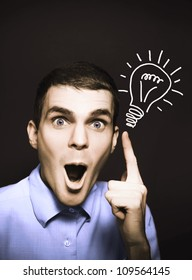 Shocked male business person pointing to light bulb illustration in a bright spark of ideas concept on dark copy space background
