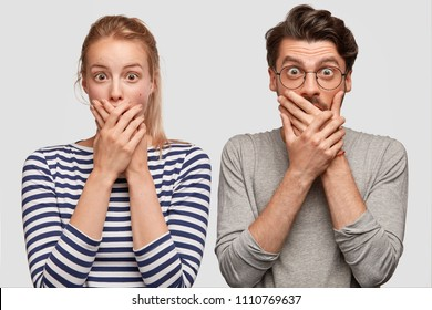 Shocked male and female teenagers cover mouth and look surprisingly at camera, hear bad news, express their reaction. Terrified European young woman and her man companion see something amazing