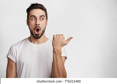 Shocked male model with stubble, keeps mouth widely opened, expresses surprisment and disbelief, shows something with thumb on blank copy space, isolated over white background. Advertising concept
