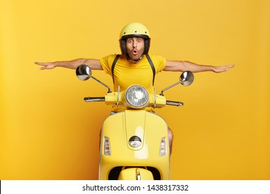 Shocked male motorcyclist travels on motorbike, has adventure trip and feels extreme, keeps hands away from handlebars, spreads sideways, likes active rest during summer, drives on high speed.