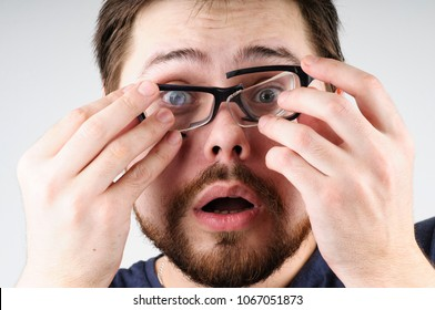 Shocked man with broken glasses on his face