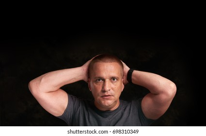shocked man with his arms on head. Black background with copy space