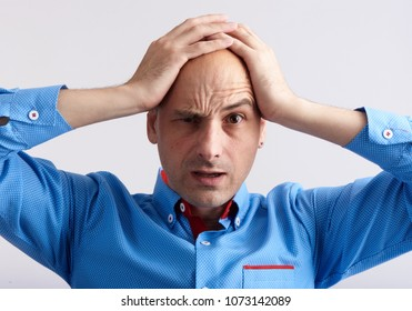 Shocked man holding his head in his hands. Studio shot