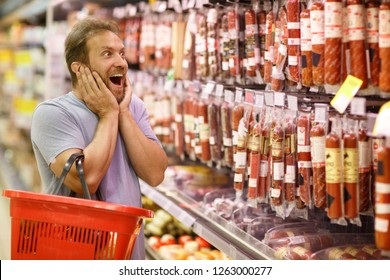 Shocked man with opened mouth holding hands on face and smiling. He looking at prices on meat products in supermarket. Bearded client holding red basket while buying food.