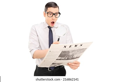 Shocked man reading the news through a magnifier isolated on white background