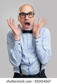 shocked man with suspenders, bow-tie and glasses. Studio shot