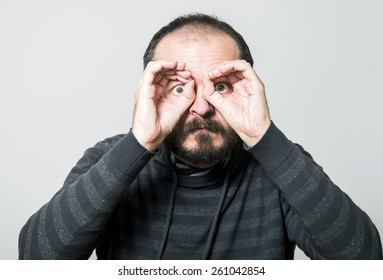 Shocked man in sweater looking through hands, making binoculars