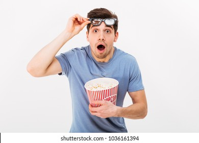 Shocked man in t-shirt and 3d glasses with popcorn looking at the camera over grey background