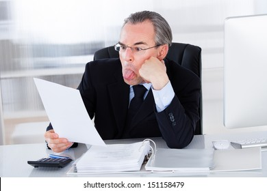 Shocked Mature Businessman Sticking Tongue Out While Holding Paper