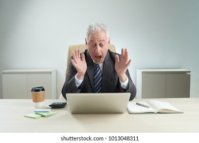 Shocked mature businessman wearing classical suit looking on laptop screen and shouting, interior of modern office on background