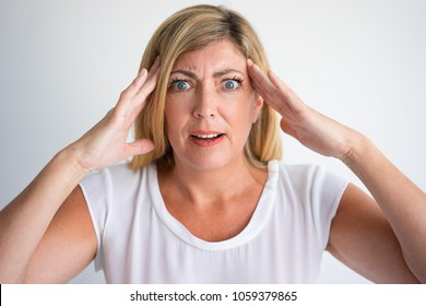 Shocked mature Caucasian woman with wide eyes and questioning face touching temples. Closeup of angry lady can not believe her eyes. Bad news or surprise concept