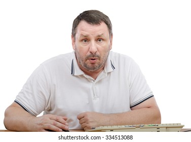 Shocked middle aged man is sitting at desk. The bearded man is wearing a white polo shirt with short sleeve. There are white shutters background behind his back