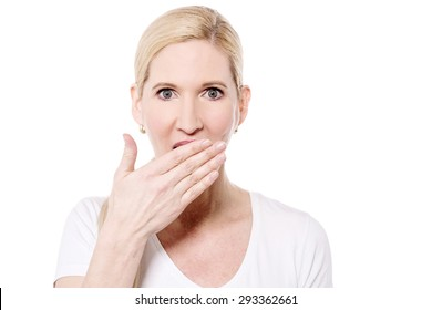 Shocked middle aged woman with hand over mouth