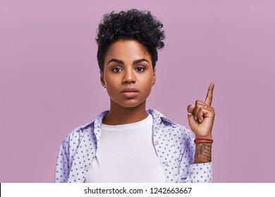 Shocked mixed race dark skinned female indicates upwards with puzzled expression, demonstrates something strange, wears fashionable clothing on lavender studio background. Advertisement concept