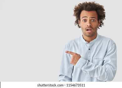 Shocked mixed race male with dark curly hair, has surprised look directly at camera, points aside with fore finger, shows blank space for your advertising content, feels embarrassed and nervous