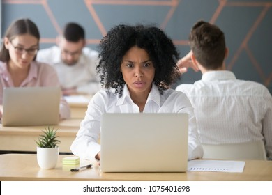 Shocked mixed race woman looking at laptop in shared office, stressed black female employee terrified reading online news, afro american student afraid of cyber bullying bad email or computer problem