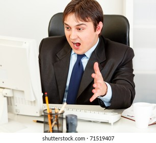Shocked modern businessman sitting at office desk and looking at computer monitor