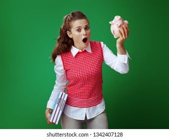 shocked modern student in grey jeans and pink sleeveless shirt with textbooks shaking pink piggy bank against green background. Financial challenges and expenditures of modern education.