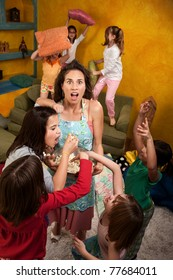 Shocked mother among wild little girls at a sleepover