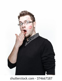 Shocked nerdy guy with footprints from red lipstick on his cheek. Concept of gratefulness girls.