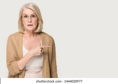 Shocked old lady showing to left at copy space blank place. Confused elderly woman attracts attention, advice, help, invite concept. Headshot of senior female in studio isolated on gray background
