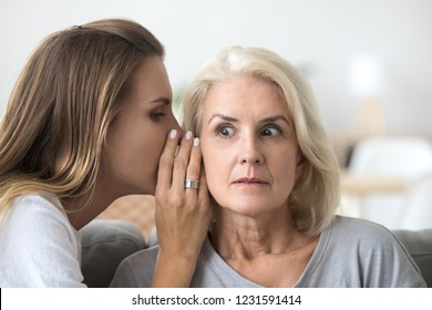 Shocked older woman listening to young female whispering in ear, friend gossiper telling secret rumors or unbelievable news to surprised senior lady, old mother and adult daughter gossiping concept