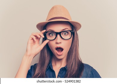 Shocked pretty woman in hat and glasses with open mouth