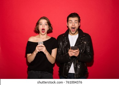 Shocked punk couple holding their smartphones while looking at the camera with open mouth over red background