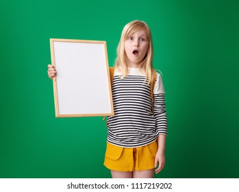 shocked pupil with backpack showing blank board against green background