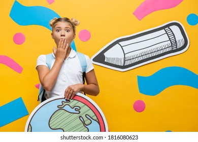 shocked pupil covering mouth with hand while holding globe maquette near paper pencil and decorative elements on yellow