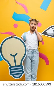 shocked pupil touching face while holding light bubble maquette on yellow background with decorative elements and paper pencil