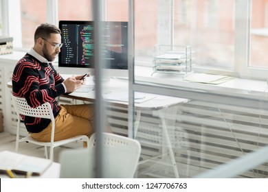 Shocked puzzled handsome male coding expert in glasses sitting at table with powerful computer and reading sms on phone