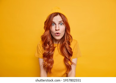Shocked redhead girl stares speechless at camera has starled face expression opens mouth from amazement wears hat casual t shirt isolated over vivid yellow background. Monochrome shot. Omg concept