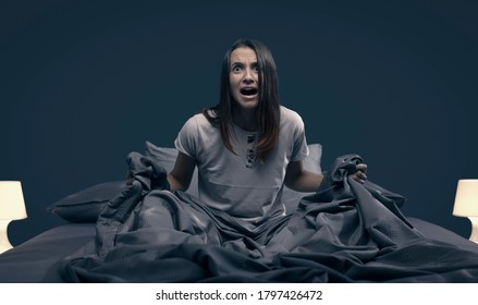 Shocked scared woman waking up from a nightmare in her bed at night